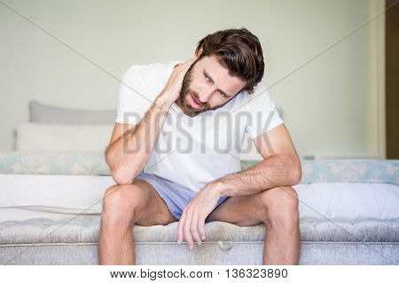 Worried man sitting on bed at home