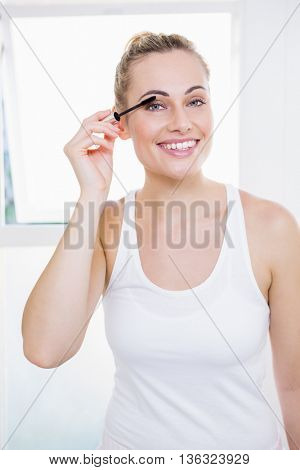 Young woman applying mascara in bathroom at home