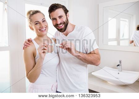 Portrait of happy couple checking pregnancy test in bathroom