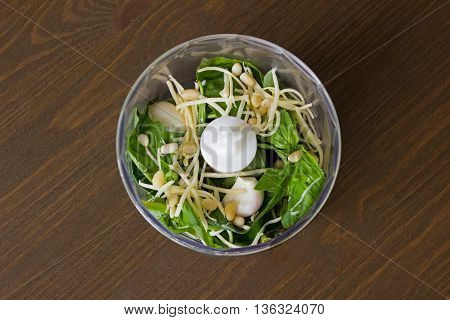 Overhead View of Making Pesto with Fresh Herbs and Oil on Wooden Background