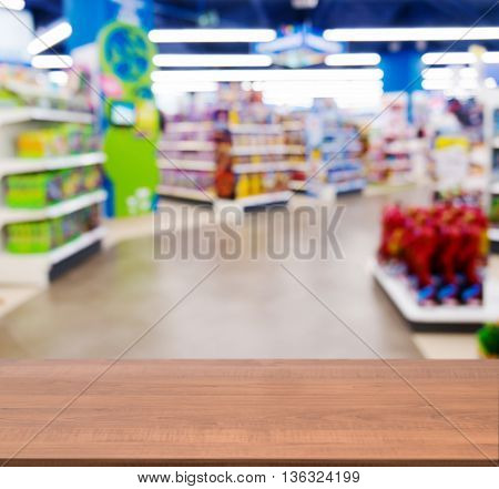 Wooden board empty table in front of blurred background. Perspective dark wood table over blur in kids toy store. Mock up for display or montage your product.