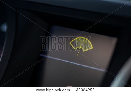 Close-up shot of a car's dashboard with the wind screen washer icon lit.
