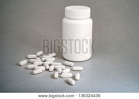 White plastic medicine bottle with pills on gray background