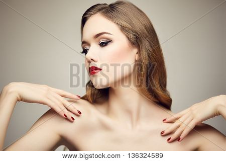 Fashion portrait of gorgeous young blond woman with red lips flirting with camera. Shallow depth of field