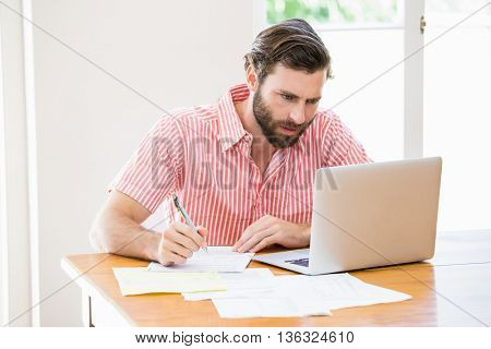 Young man using laptop while calculating a bills at home