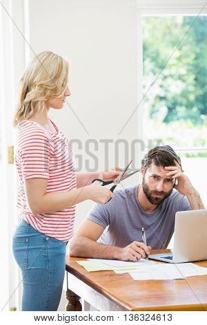 Woman cutting a credit card while tense man with bills sitting at table at home
