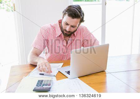 Young man calculating his bills at home