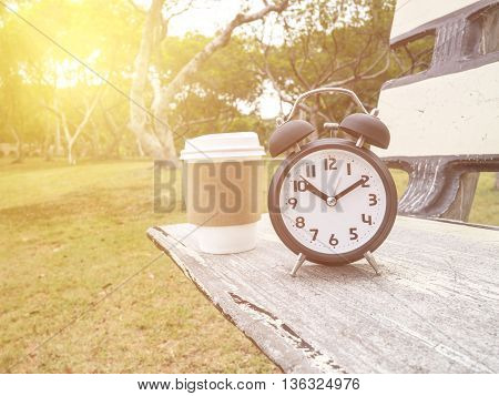 Black alarm clock and hot paper cup of coffee on wooden bench the park under sunlight with warm / soft color tone (Brake time)