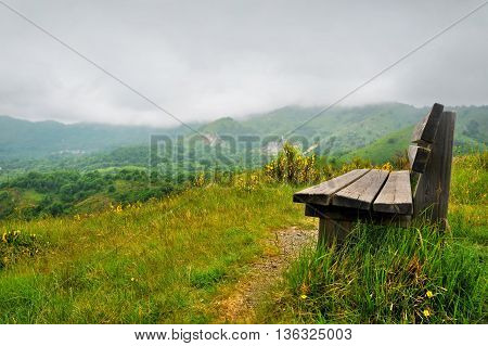 Lonely bench on a hill with mountain scenery around