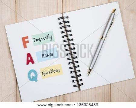 Word spell FAQ and handwriting frequently asked questions on notebook with sticky note on wood background