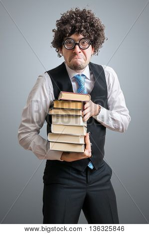 Funny nerd student is holding books in hands.