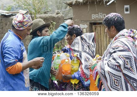 October 22 2012 Paru Paru Peru: Traditional Quechua Wedding Ceremony. Indigenous woman putting confetti on the bride`s mother hair.