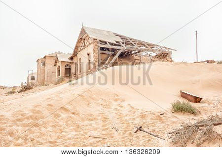 A rusty old bathtub on a dune and the ruins of buildings at Kolmanskop near Luderitz in Namibia