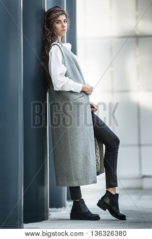 Stylish girl with beautiful hairstyle leans on the column on the wall background. She wears a gray coat without sleeves, a white blouse, dark jeans and black shoes. She holds the coat with right hand and looks into the camera. Her left leg is on the toe,
