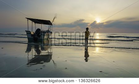 fishing boat and boy on the beach at sunrise