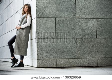 Attractive girl with beautiful hairstyle leans on the gray wall. She wears a gray coat without sleeves, a white blouse, dark jeans and black shoes. She holds the coat with her hands and looks the side. Her right leg is on the toe. Photographed from the si