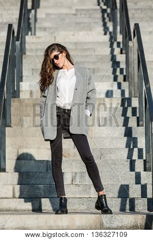 Gorgeous girl with beautiful hairstyle stands on the stair. She wears a gray coat, a white blouse, dark jeans, black shoes and sunglasses. She holds her hands in the pockets. Her head partially turned to the right. Outdoors. Horizontal.