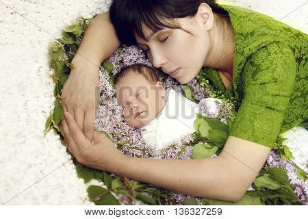 young mother sleeps with a newborn child embracing it in the colors of lilac and green dress