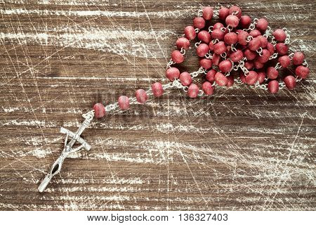 Old wooden scratched background and catholic rosary