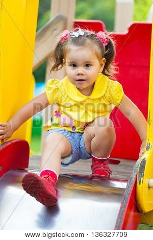 smiling little  girl is sitting on a children's slide. She has fun on playground