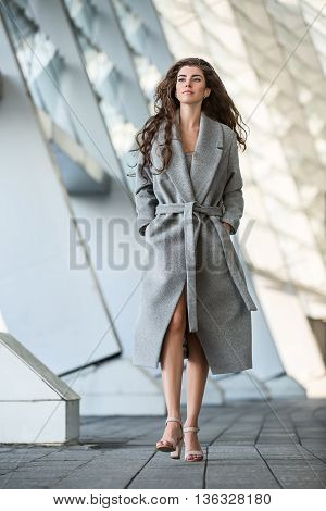Thoughtful girl with beautiful hairstyle walks outdoors on the blurry urban background. She wears a gray coat with a belt and beige sandals. She holds her hands in the pockets. She looks in front of herself. Vertical.