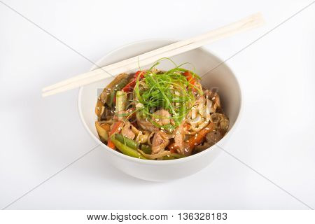 Beef wok noodles with chopsticks in a white bowl