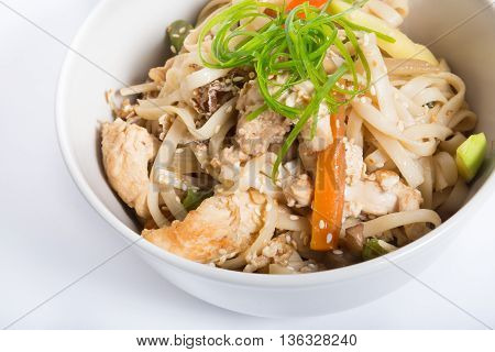 Chicken noodles wok served in a white bowl