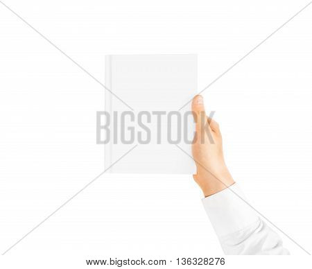 Hand in white shirt sleeve holding closed blank book cover mockup in the hand. Vertical catalogue template mock up hold in arm. Clear surface booklet notebook cover presentation. Textbook catalog.