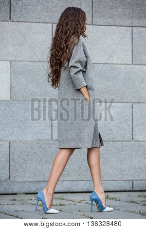 Trendy girl with beautiful hairstyle stands sideways on the gray wall background. She wears a gray coat and blue-white shoes. She holds her right hand in the pocket. Outdoors. Vertical.