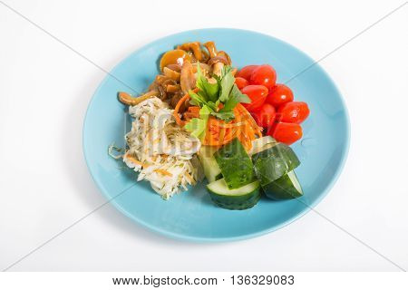 Pickled vegetables and mushrooms on a blue plate
