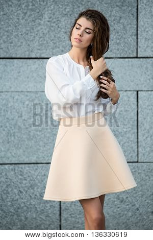 Beautiful girl with beautiful hairstyle stands on the gray wall background. She wears a white blouse and a beige skirt. She holds her hair with the hands. She has rings on the right hand. Her eyes are closed. Vertical.