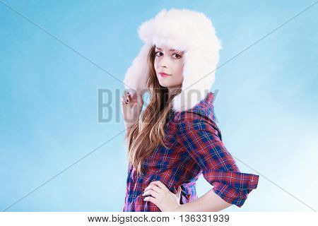 Winter fashion. Close up young woman wearing fashionable wintertime clothes white fur cap studio shot on blue background