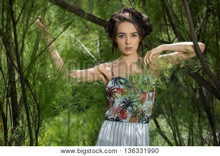 Sexy girl in a dress stands between trees on the background of trees. Dress is with silver bottom and flowered top. She holds the tree with the right hand and looks into the camera with parted lips. Her left arm is bent at the elbow and pressed to the oth
