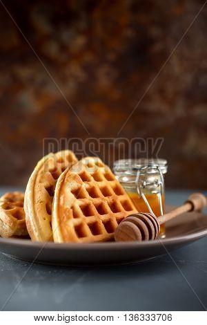 Fresh Belgium waffles. Waffle with honey, rustic background, toned