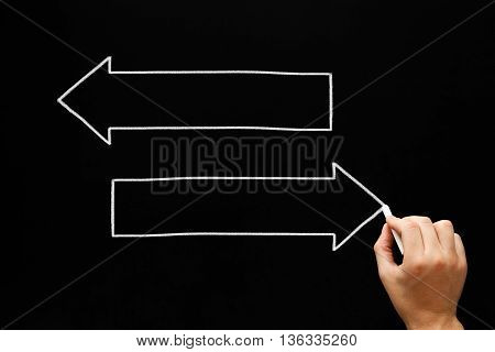 Hand drawing two blank arrows with white chalk on blackboard. Copy space for text on the arrows.