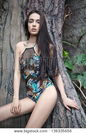 Brunette girl leans on the big tree. She wears a colorful swimsuit with pictures. She holds the right hand on the right leg, left hand is on the tree. She looks into the camera with parted lips. Vertical.