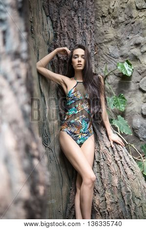 Gorgeous girl leans on the big tree. She wears a colorful swimsuit with pictures. She holds right hand near the head, left hand is on the tree, legs are crossed. She looks into the camera with parted lips. Vertical.