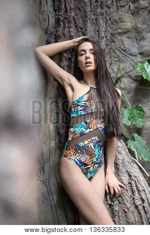Stylish girl leans on the big tree. She wears a colorful swimsuit with pictures. She holds right hand on the head, left hand is on the tree, legs are crossed. She looks into the camera with parted lips. Vertical.