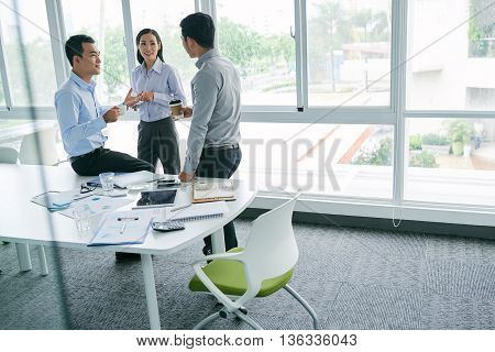 Asian coworkers chatting during short coffee break