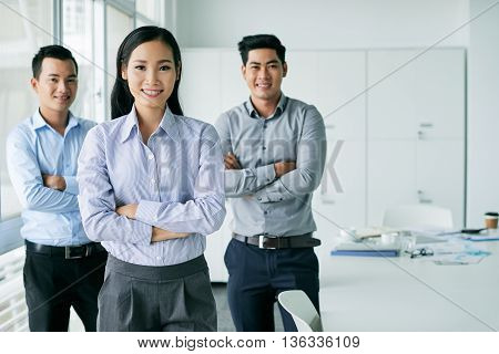 Portrait of confident Vietnamese business team standing in office