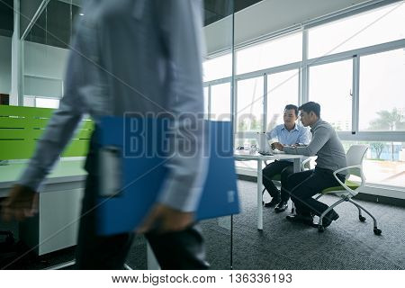 Two businessmen discussing their ideas at table in modern office
