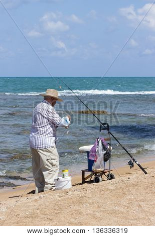 Acre Israel - May 28 2016: Elderly man fishing with a fishing rod on the beach in Akre Israel