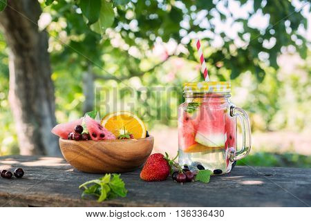 Summer drink with watermelon and berries on a wooden table in the garden