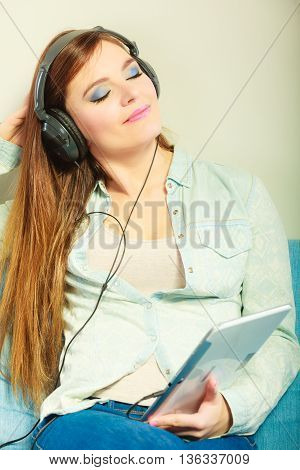 Modern technology leisure concept. Young attractive woman with headphones closed eyes relaxing using tablet