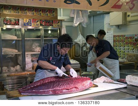 TOKYO-JAPAN, 27 June 2016: Man preparing tuna fish at the fish market in Tokyo, Japan.  It is the biggest wholesale fish and seafood market in the world.