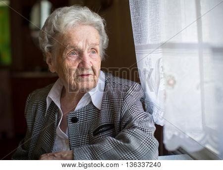 An elderly woman, sitting at the table, a portrait.