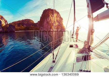 Young lady standing on the bow of yacht and looking to the rocky island at sunrise