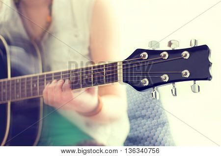 close up shot of strings and guitarist hands playing guitar over black - shallow DOF with focus on guitar