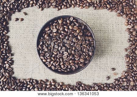 Burlap texture with coffee crop in a bowl background, plenty of robusta beans in plate. Sack cloth canvas with copy space. Frame of seeds at hessian textile