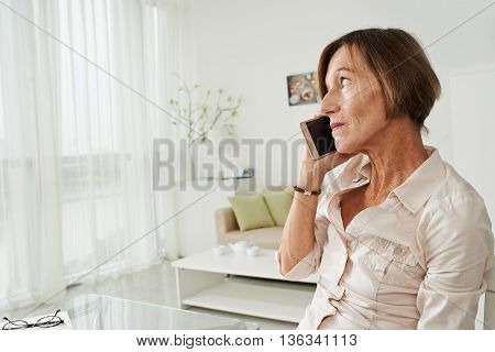 Middle-aged woman talking on phone at home